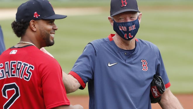 Red Sox shortstop Xander Bogaerts laughs with interim manager Ron Roenicke (right) during baseball training camp at Fenway Park, Monday, July 6, 2020, in Boston.