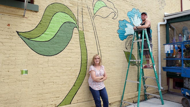 Linda Vietmeyer, left, and Mike Meade pose in front of the mural they are painting on the side of Deininger Floral on Thursday, Aug. 27, 2020, in downtown Freeport.
