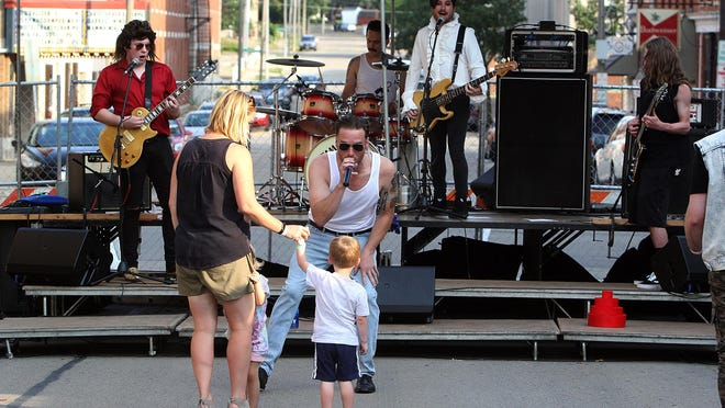 Mike Marten, lead singer for the band Flaccid Pickle, sings a song to Archie Damin as the boy holds the hand of his mother, Angie, during Music on Chicago on Friday, Aug. 3, 2018, in downtown Freeport. The group will be performing virtually for Music on Chicago on from 7 to 8 p.m. Friday, June 5 on Music on Chicago events page on Facebook