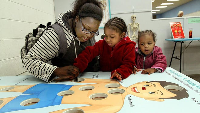 Elizabeth LaBorn of Freeport plays Operation with daughters Olivia, center, and Anastasia at the opening of the Children's Hands-On Museum on March 22, 2019, at the Lincoln Mall in Freeport. Plans for a one-year celebration this year were nixed because of the coronavirus pandemic, and the museum won't reopen until October at the earliest.