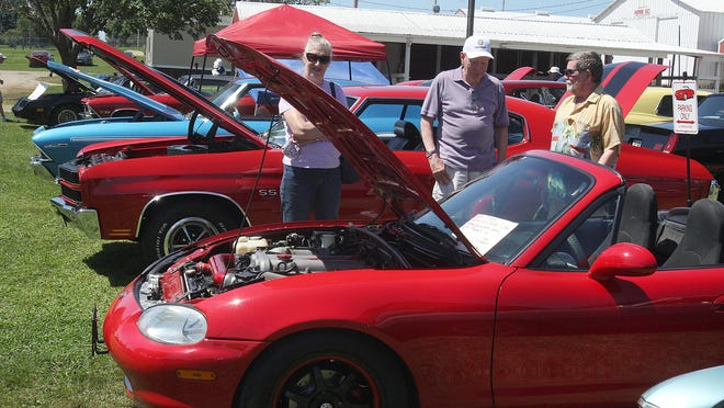 Marilyn Nolan, left, of Lanark looks at a 1999 Mazda Miata as her husband Terry Nolan, center, talks to the car owner, Dale Weber, of Freeport during the Cedarville Lions Club Ricky M Dog and Pony Car Show on Sunday at the Stephenson County Fairgrounds in Freeport.