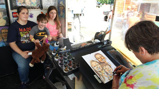 Teri Runte Peacock, right, airbrushes a drawing of Tonia Pridie,  of Belvidere, with her son, Robert Pridie, and her daughter, Hailey Matz, on Saturday at the Stephenson County Fairgrounds in Freeport.