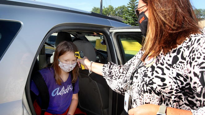 Center Elementary School principal Amanda Hayes, right, takes Brooklelyn Robertson's temperature as she arrives for school on Wednesday in Freeport.