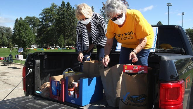 Enid Bahnub, left, and Pat Erickson-Miller sort through donated food items during a Prince of Peace Lutheran Church sponsored food drive on Sunday, Sept. 13, 2020, at Read Park in Freeport.
