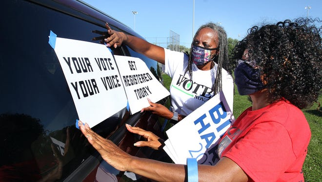 Georgina Haynes, right, and Sarah Weathersby place signs on the side of a van during a voter rally and caravan on Saturday at Taylor Park in Freeport.