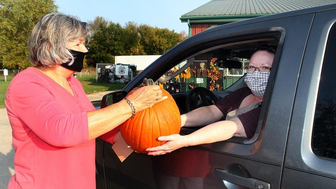 Kris Piper, right, of Dakota reaches for a pumpkin from Jodie Modica during a drive-though pumpkin buy on Saturday at Friends Forever Humane Society in Freeport.