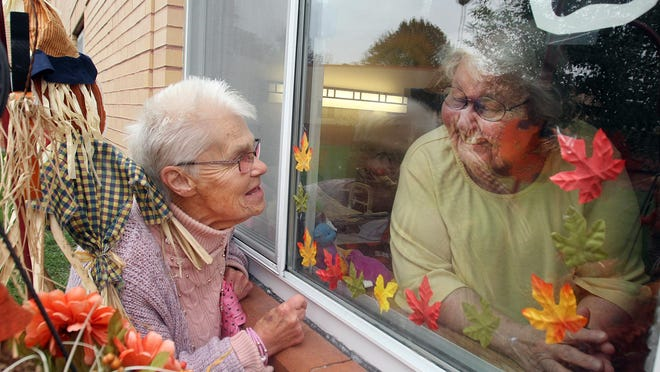 Pinkie McCourt, left, visits with Helen Derrer through the window on Sunday, Oct. 25, 2020, at Presence Saint Joseph Center in Freeport. McCourt decorates the outside for several residents who are unable to be outdoors during the COVID-19 pandemic.