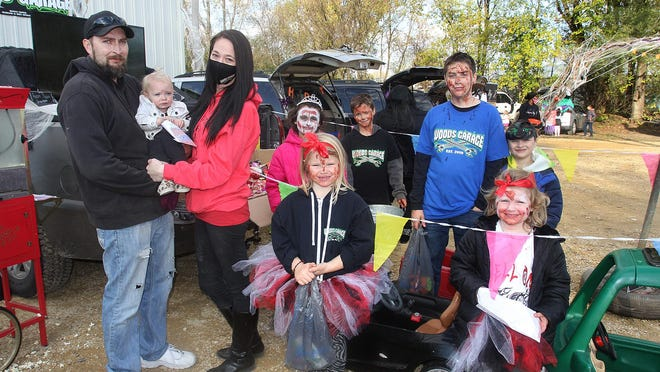 Nakita Woods, second from left, with her husband, Jason, who's holding their daughter, Gianna, and the rest of their blended family during Saturday's Trunk or Treat event at Woods Garage in Freeport.