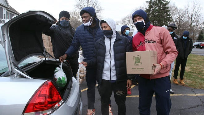 Athletes from the Highland Community College men's basketball team place food items in the trunk of a car on Saturday during the Thanksgiving Dinner Box Giveaway held at Zealous Art Studio in Freeport.