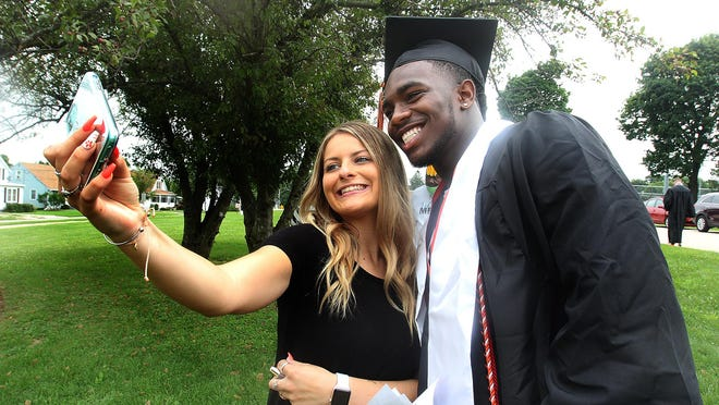 Matthew Chavers III, right, smiles for a selfie with Emily Torrisi after he crossed the stage during a graduation ceremony on Saturday at Freeport High School in Freeport.