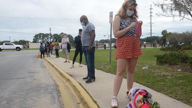 People wait in line outside the Chatham County Board of Elections Office on Monday, the first day of early voting.