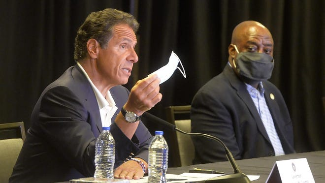 New York Gov. Andrew Cuomo waves a mask to make a point during a news conference at the Hyatt in Savannah on Monday. Listening in is Savannah Mayor Van Johnson.