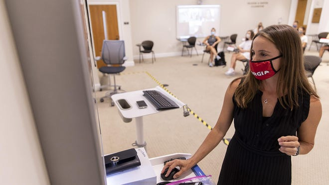 Synovus Director of the Institute for Leadership Advancement and Associate Professor Laura Little talks with her students on Zoom as she teaches her class in Benson Hall on the first day of class of the fall semester.