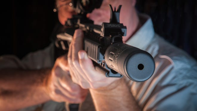 Firearms suppressors, like the one shown by Doug Williamson at The Gun Shoppe in Montgomery, are now legal for hunting in Alabama as long as the hunter has legally purchased the suppressor and carries the federal tax stamp required for all such devices.