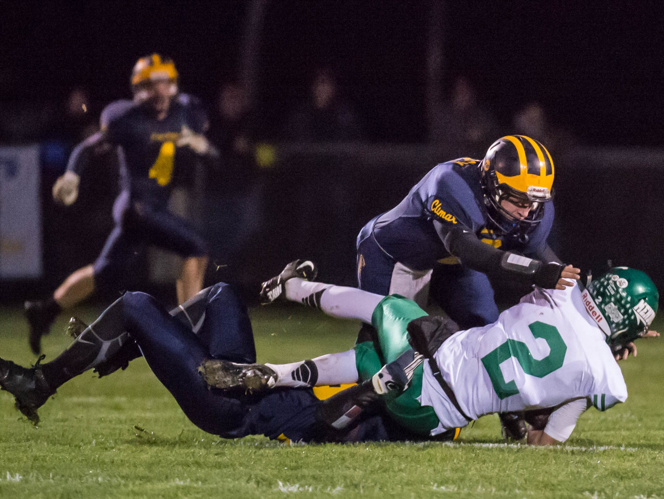 Climax-Scotts's Zackary Mobley tackles the Mendon player Friday evening.