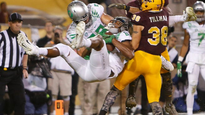 Oregon's Dwayne Stanford makes a catch colliding with teammate Johnny Mundt in the end zone over ASU's Jordan Simone to tie the game with 12 seconds left at Sun Devil Stadium in Tempe on Oct. 30, 2015.
