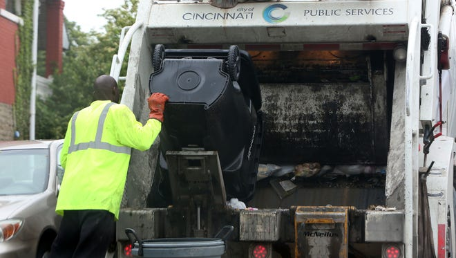 A city of Cincinnati worker collects trash in Avondale