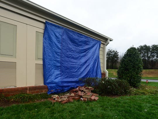 A tarp covers a whole in a building after a car accident at The Woodlands at Furman off of Arboretum Lane.