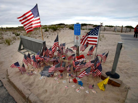 A patriotic memorial grows at D Street and Ocean Avenue in Seaside Park, NJ, and is shown Monday evening September 26, 2016.  A pipe bomb placed in a trash can here exploded on Saturday, September 17, before runners on the boardwalk were set to pass here.