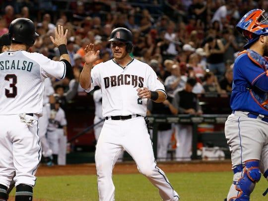 Jeff Mathis scores during Arizona's four-run third inning Tuesday.