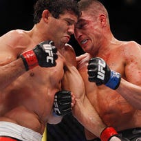 Gilbert Melendez (red gloves) fights against Diego Sanchez (blue gloves) in their lightweight bout during UFC 166 at Toyota Center