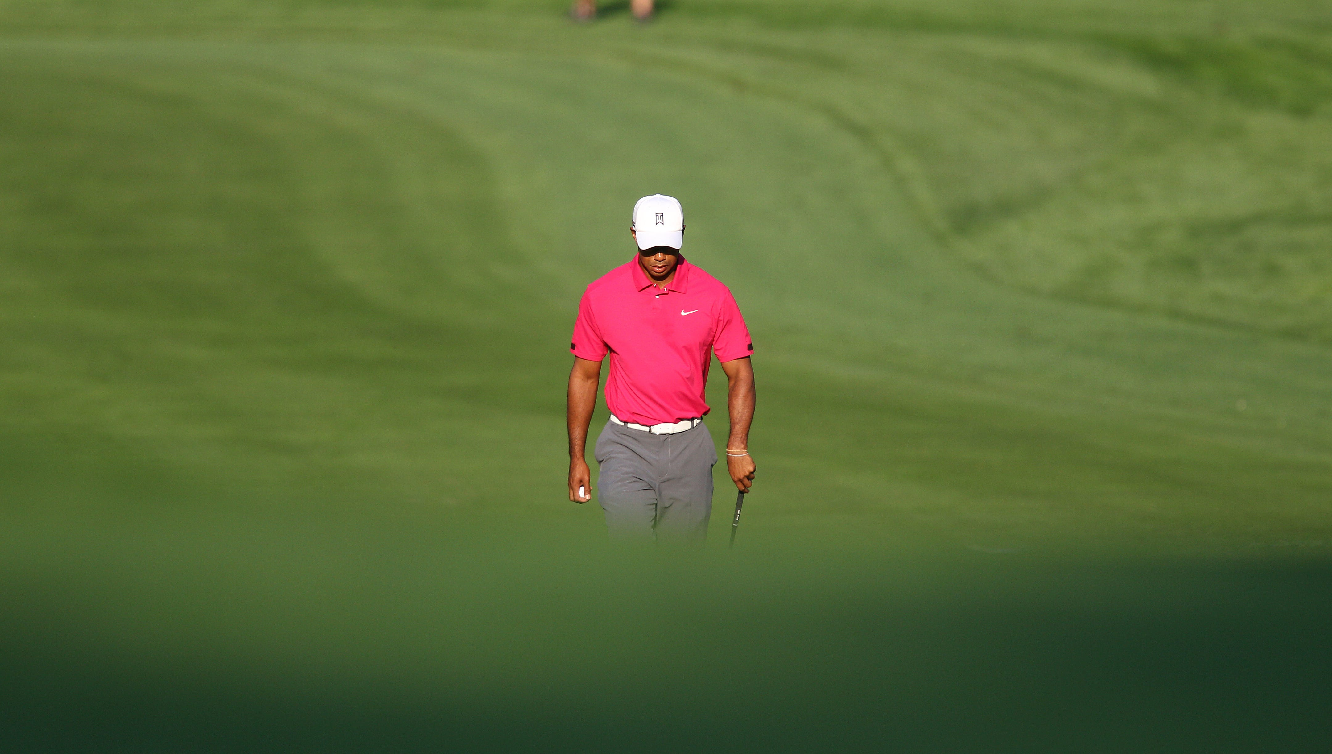 Tiger Woods makes his way up the second fairway while playing a practice round with Hunter Mahan.