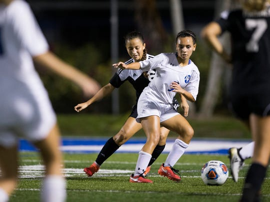 Barron Collier's Autumn Rogers, center, passes the ball in the second half of action at Barron Collier High School Thursday, Jan. 26, 2017 in Naples. Barron Collier would win 1-0.