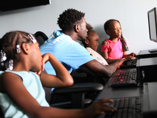 Austin Harris plays with kids on the computer at the H. Fletcher Brown Boys and Girls Club in Wilmington Monday.