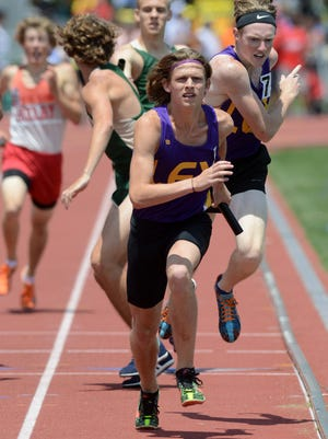 Bailey Stach takes off after receiving the baton from teammate Ryan Johnston as they help Lexington win the 4x800 relay in the Division II finals Friday at Jesse Owens Stadium in Columbus.
