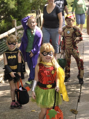Breanna Hensley, 4, is dressed a Robin, and Bailey Hensley, 4, is dressed as Batman, so they can torment their big brother, Logan Hensley, 7, who is dressed as the Joker, while they explored last year?s Boo at the Zoo entertainment with Ashton LaBerge, 6, dressed as Iron Man.