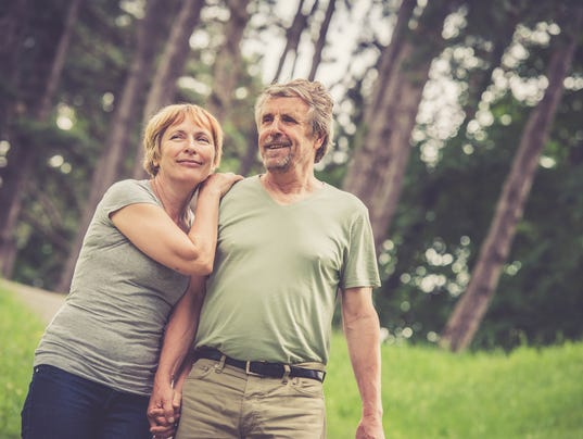 Senior caucasian couple hugging and walking outdoors in city park