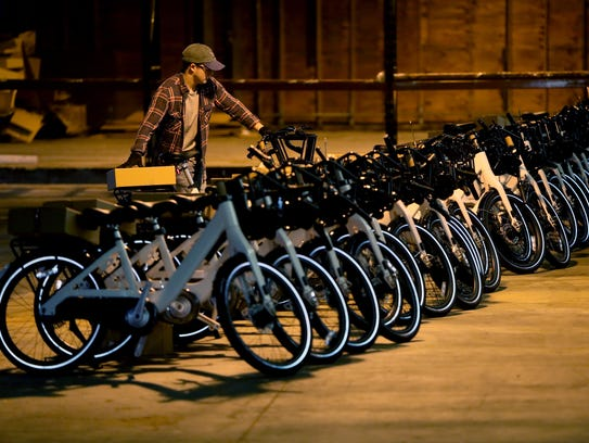 Phillip Smith adds a bicycle to a row of others as he works with a group of volunteers as they unpack a fleet of 600 bikes for the Explore Bike Share in an Uptown warehouse on Feb. 6.