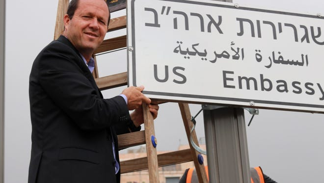 Jerusalem Mayor Nir Barkat poses with a new road sign to the new U.S. Embassy in Jerusalem on May 7, 2018, in this photo released by the Jerusalem municipality.