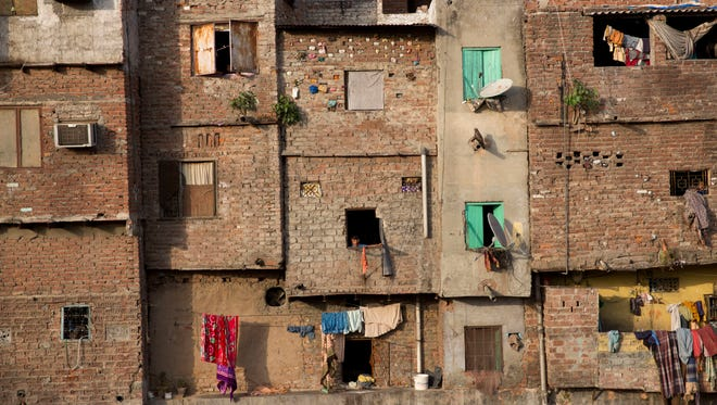 A boy looks out of a window in an impoverished area in New Delhi, India, in 2017.