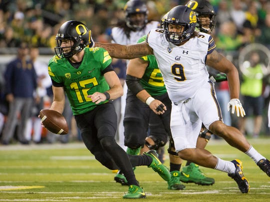 California defensive end James Looney chases down Oregon quarterback Taylor Alie during a game last season.