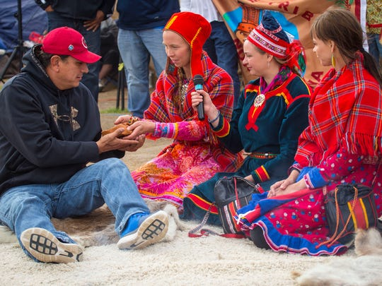 Standing Rock Sioux Chairman Frank Archambault II, left, is given a gift by Sofia Jannok, center, Inger Berit Gaup and Sara Marielle Gail, right, representing the Sami indigenous of Northern Europe during a gathering in the main fire circle at Oceti Sakowin Camp near the Standing Rock reservation Friday, Sept. 30, 2016, near Cannon Ball, N.D.