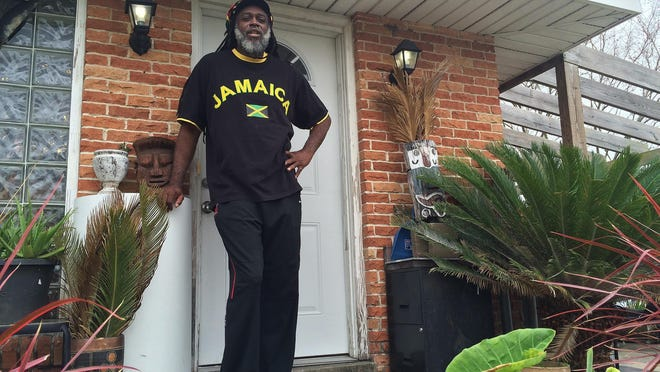 In this March 10, 2016 photo, Baba Ken Amen, an artist and vegan caterer, poses for a photo at his home in Pontchartrain Park in New Orleans. Amen says he makes ends meet renting his art-filled, solar-powered home on Airbnb.