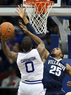 Villanova's Mikal Bridges (25) blocks the path to the basket for Seton Hall's Khadeen Carrington (0) during the second half of an NCAA college basketball game, Saturday, Feb. 18, 2017, in Newark, N.J. Villanova won 92-70. (AP Photo/Mel Evans)