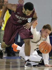Concord's Joseph Cooper (left) fights for a loose ball against Salesianum's Donte DiVincenzo in the third quarter of a DIAA state high school tournament semifinal Thursday, March 6, 2014 at the Bob Carpenter Center.
