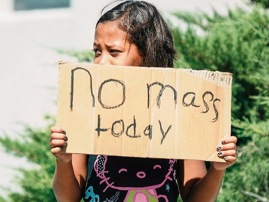 Aaliyah Doninguez, 11, stands on North Alameda Boulevard advising parishioners of Holy Cross Catholic Church that Mass is canceled on Sunday.