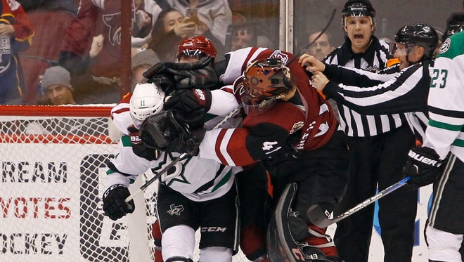 Arizona Coyotes goalie Mike Smith (41) and defenseman Anthony DeAngelo (77) tangle with Dallas Stars' Curtis McKenzie (11) after a play in front of the net during the second period of an NHL hockey game, Tuesday, Dec. 27, 2016, in Glendale, Ariz.