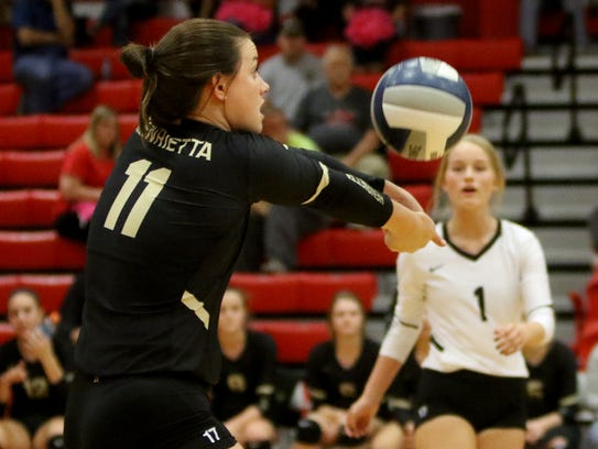 Henrietta's Maddie Brown hits the ball back over to