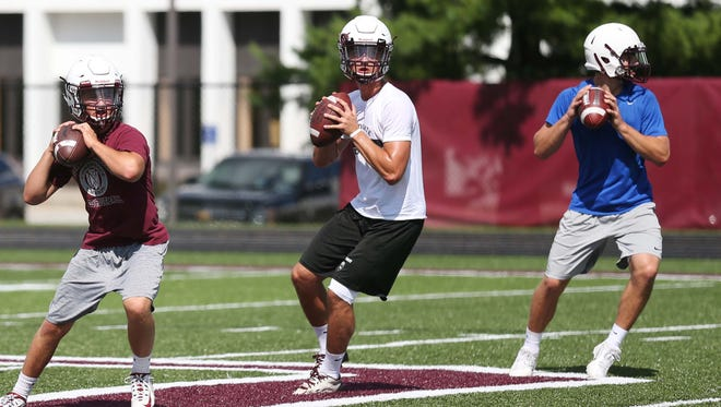 (L to R) Ben Wilson, J.T. Brown and Kurt Walding, three of four players vying for the open quarterback position at Dowling Catholic High School, run drills at practice on Monday.