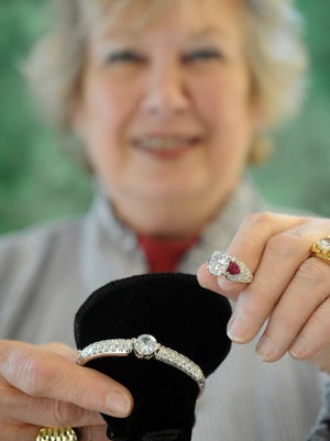 Christel Citko of Art Source Gallery holds a diamond bracelet and ring.