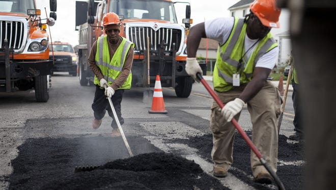 Workers patch roads at the intersection of Conant and Norwalk streets in Hamtramck in this 2015 file photo.
