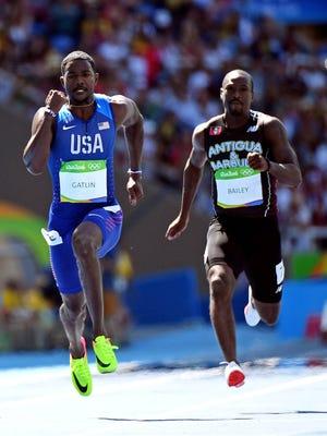 American Justin Gatlin, left, ran a 10.01 in the men's 100-meter heat Saturday.
