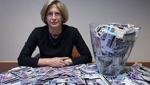 Arizona Department of Liquor assistant director Lee Hill sits beside a giant shot glass filled with hundreds of fake IDs. Fake IDs are most often confiscated in Arizona's college towns.