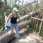 Hattiesburg Zoo employee Lisa Fields steps over a downed tree at the macaw exhibit on Sept. 8, 2005. Zoo officals said they feel fortunate the zoo sustained some damage but nothing they could not handle.