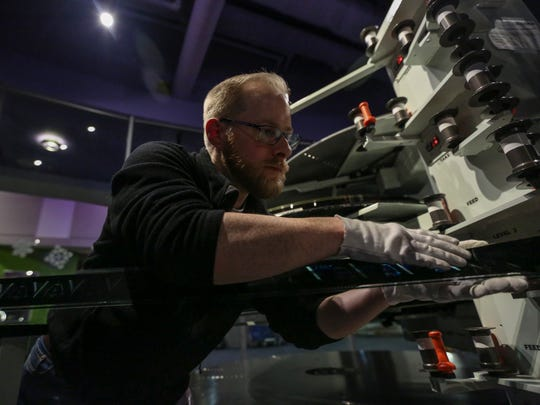 """Justin Rule, Blank IMAX's projectionist, checks a splice as he builds the 70 mm film of """"Star Wars: The Force Awakens."""""""