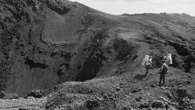"This Dec. 1970 image provided by NASA shows Apollo 15 astronauts training on the Big Island of Hawaii. Before many Apollo astronauts went to the moon, they came to Hawaii to train on the Big Island's lunar landscapes. Now, decades-old photos are surfacing of astronauts scooping up Hawaii's soil and riding across volcanic fields in a ""moon buggy"" vehicle."